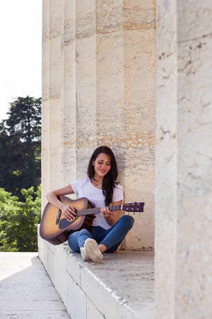 Beautiful Smiling Woman playing acoustic Guitar at Ancient Marble Temple 版權商用圖片