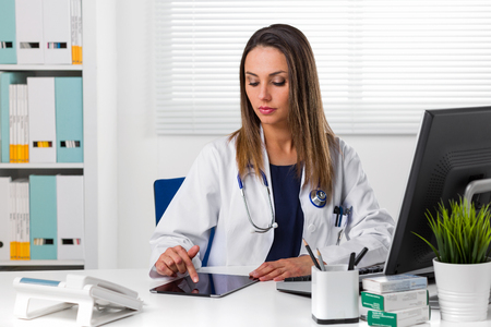 Thoughtful young attractive female doctor with stethoscope sat at desk using tablet Stock Photo
