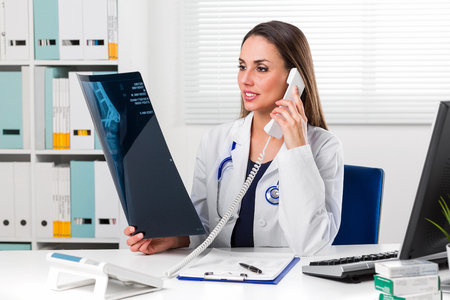 Half body Portrait of smiling Female doctor in white coat with stethoscope looking at patients x-ray in her office while speaking on the Phone Zdjęcie Seryjne