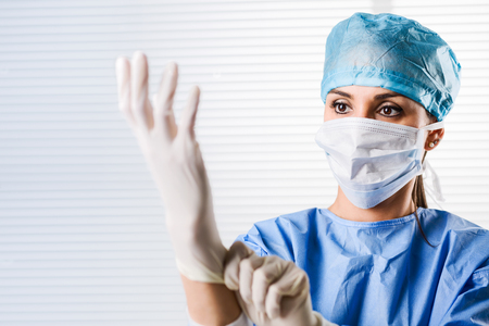 Portrait of Female doctor Surgeon in blue scrubs putting on surgical gloves Stok Fotoğraf
