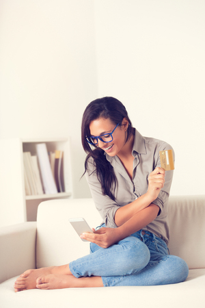 Portrait of happy woman buying online with digialt tablet and credit card on a couch at home