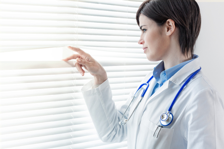 Young female doctor or nurse looking through a window parting the louver blinds with her fingers as she watches something outside 版權商用圖片