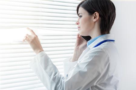 Préoccupé femme médecin réfléchie debout devant une fenêtre avec stores à persiennes regardant fixement parler sur un téléphone mobile avec copie espace Banque d'images