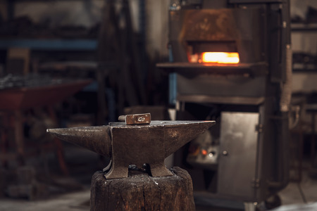 Mallet on an anvil in front of a red hot burning furnace in a metalworking workshop or blacksmith Banque d'images