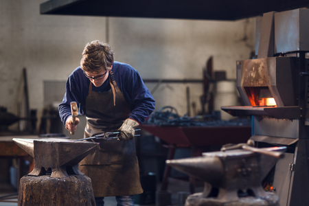 Young blaksmith working with hot metal in a metalworking workshop using specialised tongs and a hammer over an anvil with the furnace in the background