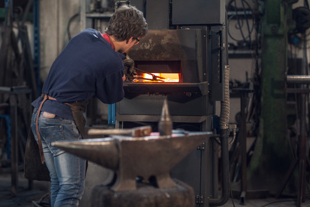 Young blaksmith working in a metalworking workshop holding a set of tongs in a burning furnace as he manufactures a bespoke object in a close up view
