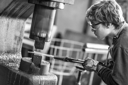 Young blaksmith working with hot metal in a workshop holding it in a mold using specialist tongs leaning forward with concentration to watch his work