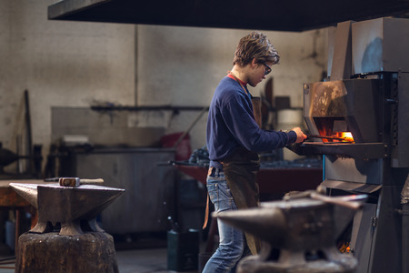 Young blaksmith working in a metalworking workshop holding a set of tongs in a burning furnace as he manufactures a bespoke object