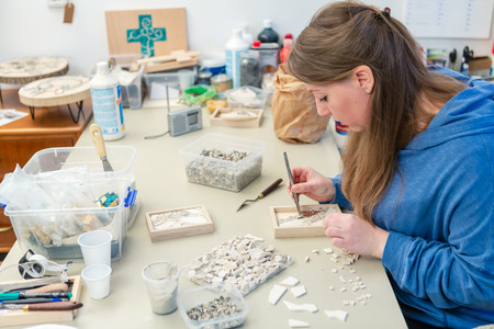 Young Female Artist working on small stones mosaic in her workshop
