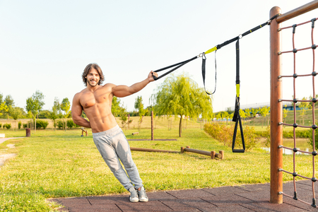 Smiling fit young man working out in a garden or park using resistance belts attached to a climbing frame to strengthen and tone his muscles leaning to the side in a health and fitness concept; suspension training concept