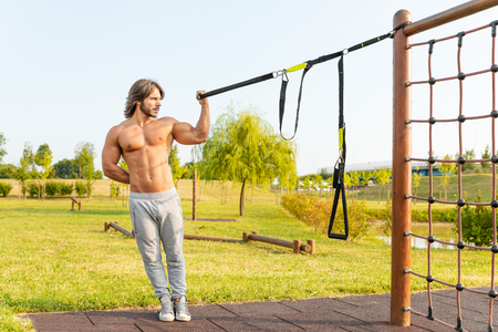 Young fit young man working out in a garden or park using resistance belts attached to a climbing frame to strengthen and tone his muscles leaning to the side in a health and fitness concept