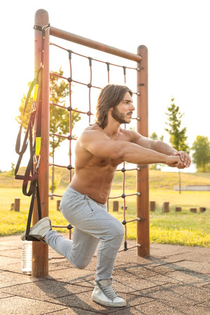 Full length side view of a handsome young man with toned muscular body exercising Bulgarian squats with the suspension trainer outdoors in the park; suspension training concept
