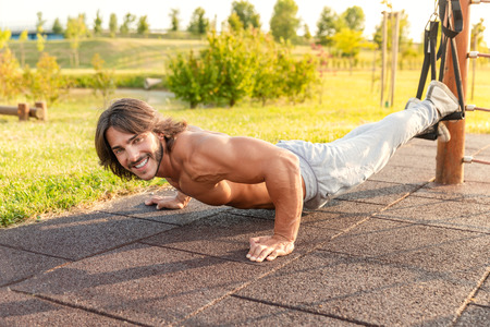 Full length of a strong and smiling young man exercising push-ups with legs hanging in the suspension trainer during intense outdoor workout