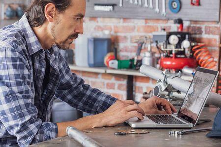 Arbeiter in einer Werkstatt, die Daten online auf einem Laptop in einer Nahaufnahme von der Seite nachsieht, die ihn an einem Schreibtisch sitzt Standard-Bild