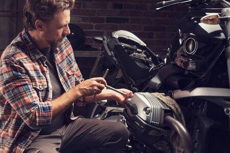 Mechaniker, der einen Steckschlüssel an einem Oldtimer-Motorrad in einer Nahaufnahme verwendet, während er Reparaturen oder Wartungsarbeiten in einer Werkstatt durchführt