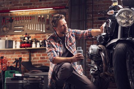 Low angle of a man polishing classic vintage motorcycle in garage or workshop, holding bottle of wax in one hand, and applying it to bike with cloth Standard-Bild