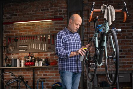 Mechanic oiling the chain on a bicycle in a neatly laid out brick workshop during servicing or repair in a close up view 스톡 콘텐츠