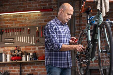Mécanicien réparant un vélo monté sur un support surélevé dans un atelier dans une vue rapprochée de lui travaillant sur la roue et la chaîne