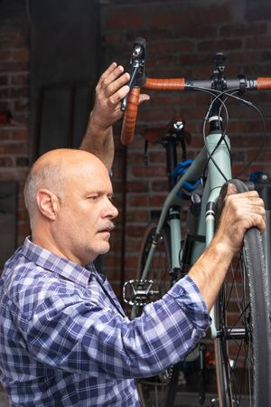 Mechanic servicing a bicycle in a workshop in a close up view on his face as he concentrates on the bike mounted to a raised stand for repairs