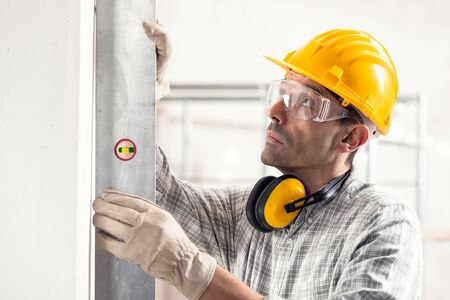 Builder; structural engineer or contractor using a large spirit level on a vertical new build wall in a house under construction in a close up view