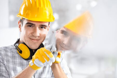 Builder wearing a hardhat and ear muffs reflected in glass he is holding with gloved hands on site smiling at the camera Stock fotó - 137972774