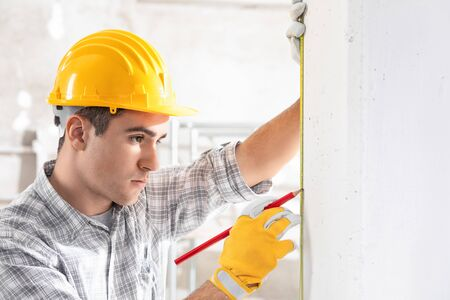 Young construction worker in yellow hardhat and gloves measuring the wall with measuring tape. Indoor front portrait with copy space 写真素材
