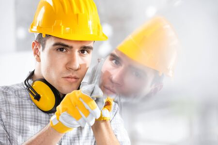 Builder wearing a hardhat and ear muffs reflected in glass he is holding with gloved hands on site Stock fotó