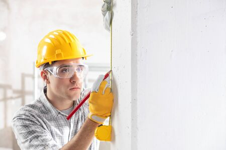 Young construction worker in yellow hardhat, safety goggles and gloves measuring the wall with measuring tape. Indoor front portrait with copy space