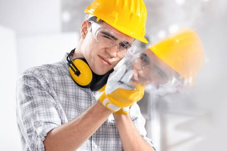 Builder wearing a hardhat and ear muffs reflected in glass he is holding with gloved hands on site Stock fotó - 137975143