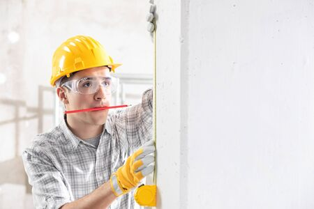 Young construction worker in yellow hardhat, safety goggles and gloves measuring the wall with measuring tape, while holding the pencil in his mouth. Indoor front portrait with copy space