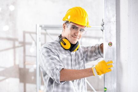 Young builder checking a vertical wall on a construction site holding up a large spirit level with a smile