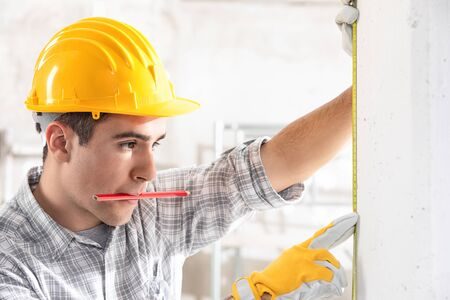 Young construction worker in yellow hardhat and gloves measuring the wall with measuring tape, while holding the pencil in his mouth. Indoor front portrait with copy space