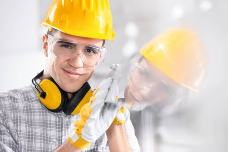 Builder wearing a hardhat and ear muffs reflected in glass he is holding with gloved hands on site smiling at the camera
