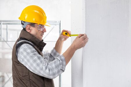 Builder making a measurement on a new interior wall with a measuring tape in a building under construction Stock Photo