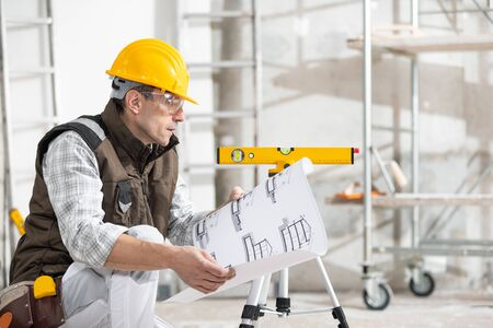 Builder, structural engineer, architect or workman in hardhat adjusting a spirit level on a tripod in a building under construction