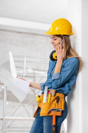 Young female engineer or architect holding a blueprint in her hand as she chats on her smartphone on site in a room under construction Stockfoto