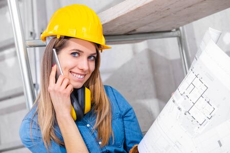 Young female engineer or architect holding a blueprint in her hand as she chats on her smartphone on site in a room under construction turning to smile at camera Stock Photo