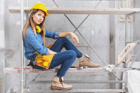 Capable young woman construction worker wearing a tool belt and hardhat sitting on interior scaffolding in a room under construction