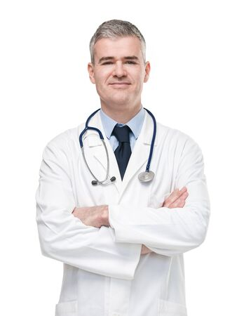 Confident male doctor in white lab coat and stethoscope standing with folded arms smiling at the camera isolated on white