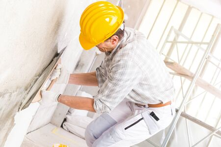 Builder applying new plaster to a wall indoors covering a damp stain during renovations and repairs in a high key close up image