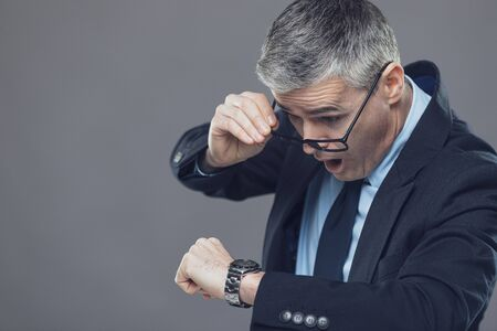 Businessman panicking after looking at the time on his wristwatch; copy space