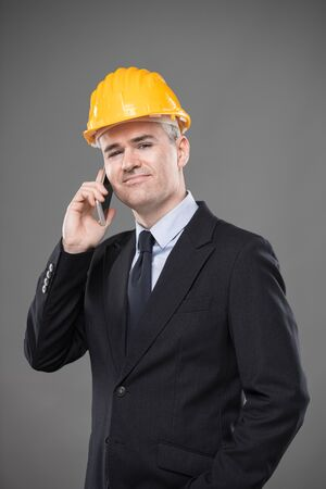 Friendly smiling architect or structural engineer in a smart suit, tie and hardhat standing chatting on a mobile phone looking at the camera with a beaming smile isolated on grey 版權商用圖片