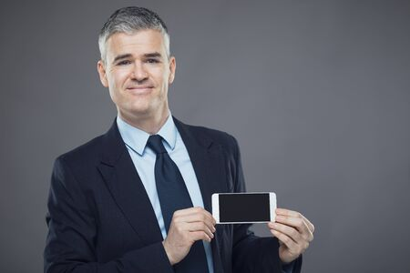 Smiling stylish confident businessman or salesman holding up a mobile phone with the blank screen to the viewer isolated on grey with copy space