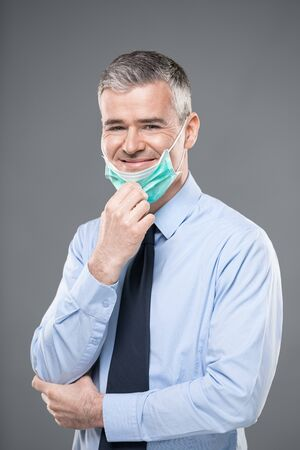 Professional man in shirtsleeves wearing a mask as protection against Corona virus or Covid-19 lowering it with his hand to smile at the camera