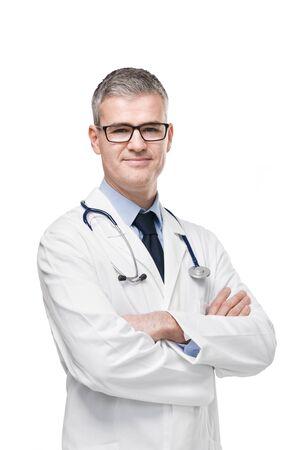 Médico varón confiado en bata blanca de laboratorio, anteojos y estetoscopio de pie con los brazos cruzados sonriendo a la cámara aislada en blanco Foto de archivo