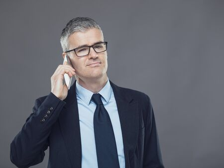 Stylish businessman listening to a mobile phone call with a serious thoughtful expression, head and shoulders isolated on grey 版權商用圖片