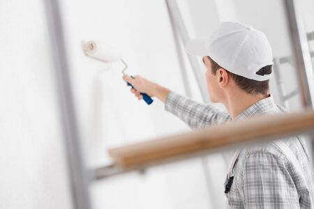 Young painter painting a white wall with a roller during renovations or construction viewed through a ladder