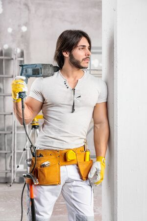Happy confident builder with drill slung over his shoulder standing leaning against a wall in a room under construction grinning at the camera
