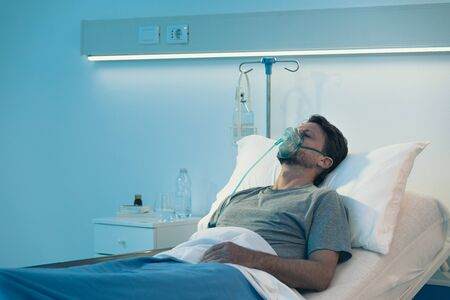Adult man lying in a hospital bed at night and he is sleeping and wearing an oxygen mask