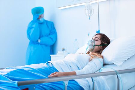 Nurse standing watch over a patient with coronavirus on a hospital ward as the woman lies in bed wearing a positive pressure oxygen mask to assist her breathing during the pandemic